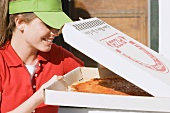 Woman in sun visor looking into opened pizza box