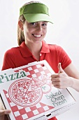 Smiling woman with pizza box, giving thumbs up sign