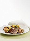 Grilled pork steaks with roast potatoes and olives