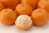 Several mandarin oranges, one half-peeled