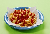 A plate of chips with a lot of ketchup