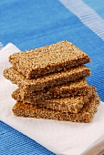Five bars of sesame brittle, stacked, on napkin