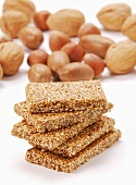 Five bars of sesame brittle, stacked, in front of nuts