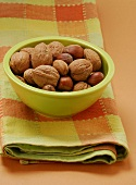 Unshelled walnuts, hazelnuts & almonds in green bowl on tea towel