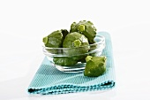 Several green patty pan squashes in glass bowl on table mat