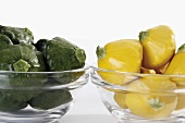 Green & yellow patty pan squashes in glass bowls (close-up)