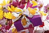 Wrapped gift with summery ribbon, chrysanthemums