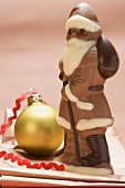 Chocolate Father Christmas beside Christmas bauble