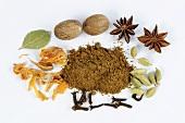 Garam masala, surrounded by cardamom, cloves, nutmeg, star anise