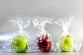 Three apples in plastic bags