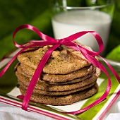 Stack of Cookies Tied with a Pink Ribbon; Glass of Milk