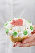 Hand holding cupcake with marzipan pig