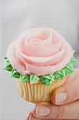 Hand holding cupcake with pink marzipan rose