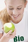 Woman eating an organic green apple