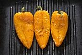 Drei gelbe Paprikaschoten in einer Grillpfanne
