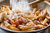 Adding Parmesan Cheese to Penne Pasta with Tomato Sauce in Saute Pan