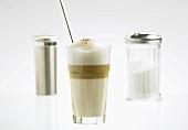 A glass of latte macchiato with sugar and cocoa shakers