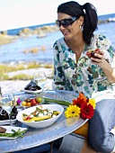 Black-haired woman picnicking by the sea