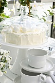 Cream cake under cake cover, coffee cups