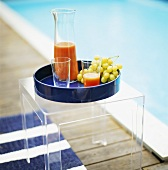 Fruit juice and grapes on tray by swimming pool