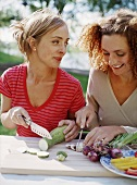 Two women slicing vegetables out of doors