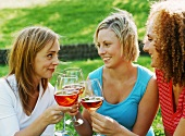 Three friends clinking glasses of rosé sparkling wine