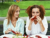 Two women eating crayfish out of doors (Crayfish party, Sweden)