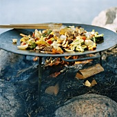 Meat and vegetables in wok on open fire