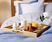 Breakfast tray with croissant, egg and juice on bed