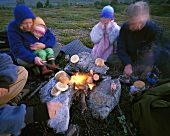 Family with small children cooking over campfire