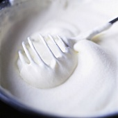 Whipped cream with whisk in a bowl