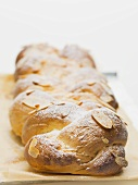 Bread plait with flaked almonds & icing sugar on baking parchment