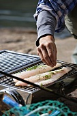 Man grilling fish at water's edge (Sweden)