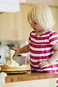 Small blond girl baking a cake