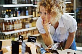 Woman at cheese counter in supermarket (Sweden)