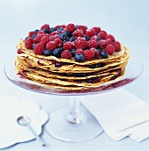 Pancake cake topped with raspberries and blueberries