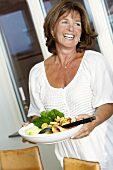 Laughing woman holding plate of vegetables