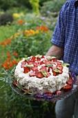 Man serving strawberry cream cake in garden