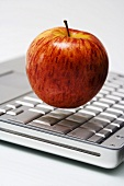Red apple hovering over laptop