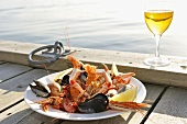 Plate of seafood on landing stage by sea