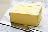 Block of butter on paper, knife beside it