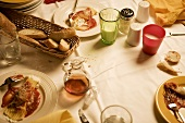 Pasta dish (manicotti) and bread on laid table (Italy)