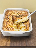 Potato gratin in baking dish with piece on server