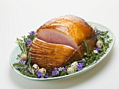 Glazed roast ham surrounded by herbs, for Easter