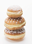 Three doughnuts dusted with icing sugar, stacked