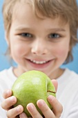Little boy holding green apple