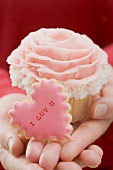 Hands holding cupcake and Valentine's Day biscuit