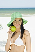 Junge Frau mit Sommerhut und grünem Apfel am Strand