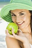 Junge Frau mit Sommerhut und grünem Apfel