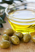 Green olives and a small bowl of olive oil